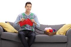 Homme heureux s'asseyant sur un sofa et un tricotage photos libres de droits