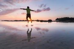 Homme heureux sautant dans l'eau Photographie stock libre de droits