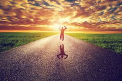 Homme heureux sautant sur la longue route droite, manière vers le soleil de coucher du soleil Image libre de droits