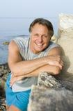Homme heureux se penchant sur une roche Photographie stock libre de droits