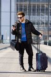 Homme heureux se tenant à la station avec le sac et le téléphone portable Photo stock
