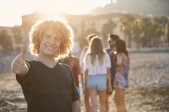 Homme heureux se tenant sur la plage avec des amis montrant le pouce  Photographie stock