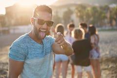 Homme heureux se tenant sur la plage avec ses amis se dirigeant à l'appareil-photo Photos libres de droits
