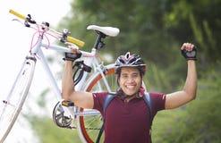 Homme heureux soulevant un vélo Photo libre de droits