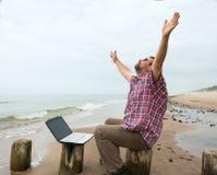 Homme heureux supérieur s'asseyant à la plage avec l'ordinateur portable photos libres de droits
