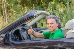 Homme heureux sur la voiture convertible Photographie stock