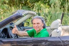 Homme heureux sur la voiture convertible Image stock