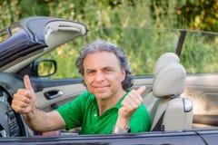 Homme heureux sur la voiture convertible Photographie stock libre de droits