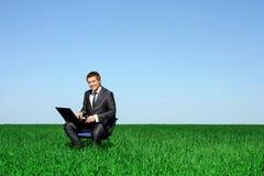 Homme heureux sur la zone avec l'ordinateur portatif photographie stock