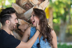 Homme heureux tenant l'arbre proche avec l'amie touchant son visage Photographie stock