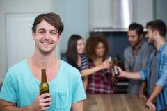 Homme heureux tenant la bouteille à bière tandis qu'amis à l'arrière-plan Images libres de droits