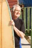 Homme heureux tenant la planche de surf tout en se tenant contre la hutte de plage Photo stock