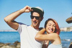 Homme heureux tenant le chapeau se tenant avec l'amie sur la plage Photo libre de droits