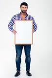 Homme heureux tenant le conseil vide Image stock
