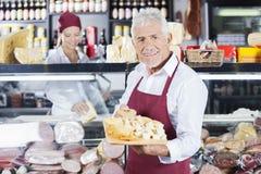 Homme heureux tenant le divers fromage à bord de stock Photographie stock libre de droits