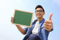 Homme heureux tenant le tableau noir Photos stock