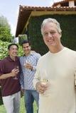Homme heureux tenant le verre de vin Image stock