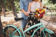 Homme heureux tenant sa main d'amie sur le volant de bicyclette avec les fleurs colorées Photos libres de droits