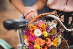 Homme heureux tenant sa main d'amie sur le volant de bicyclette avec les fleurs colorées Photo stock