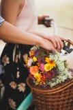 Homme heureux tenant sa main d'amie sur le volant de bicyclette avec les fleurs colorées Image stock