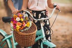 Homme heureux tenant sa main d'amie sur le volant de bicyclette avec les fleurs colorées Photographie stock libre de droits