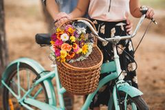 Homme heureux tenant sa main d'amie sur le volant de bicyclette avec les fleurs colorées Image libre de droits