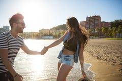 Homme heureux tenant son amie à la main au bord de la mer Images stock
