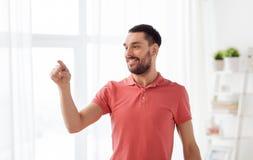 Homme heureux touchant quelque chose imaginaire à la maison photos stock