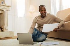 Homme heureux travaillant avec des papiers et sur son ordinateur portable Image libre de droits