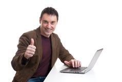 Homme heureux travaillant sur l'ordinateur portatif Photo libre de droits