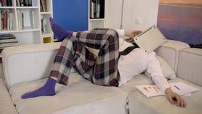 Homme heureux travaillant sur son ordinateur portable sur le sofa à la maison banque de vidéos