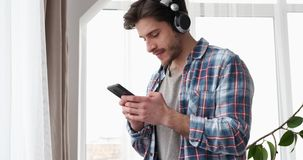Homme heureux utilisant le téléphone portable tandis que musique de écoute sur des écouteurs clips vidéos