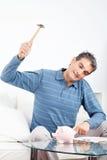 Homme heurtant la tirelire avec le marteau Photo libre de droits