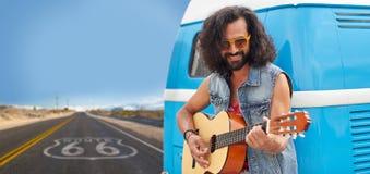 Homme hippie jouant la guitare au monospace sur l'itinéraire 66 photos stock