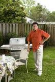 Homme hispanique à côté de gril d'arrière-cour Photographie stock