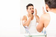 Homme hispanique éclaboussant l'eau sur son visage Images libres de droits