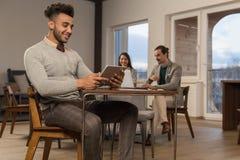 Homme hispanique d'affaires employant des hommes d'affaires de tablette dans la pause-café de café de centre de Coworking images stock