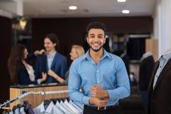 Homme hispanique de sourire heureux d'affaires utilisant la nouvelle chemise tout en faisant des emplettes dans le magasin de vêt photos libres de droits
