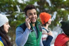 Homme hispanique employant l'hiver extérieur de Forest Young People Group Walking de neige futée d'appel téléphonique Images stock