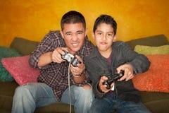 Homme hispanique et garçon jouant le jeu vidéo images libres de droits