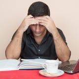 Homme hispanique fatigué étudiant à la maison Images libres de droits