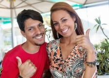 Homme hispanique heureux avec l'amie montrant des pouces  Images libres de droits