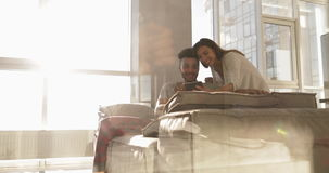 Homme hispanique heureux Sit On Coach Asian Woman de jeunes couples de métis à l'aide de la tablette ensemble clips vidéos