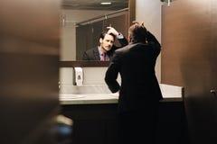 Homme hispanique inquiété d'affaires regardant le délié dans des toilettes de bureau image libre de droits
