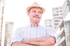Homme hispanique supérieur retiré avec le chapeau se tenant et souriant images stock