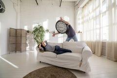 Homme-horloge réveillant la fille qui se trouve sur le divan dans le grenier Photographie stock