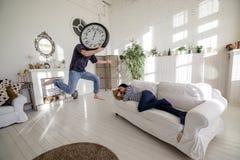 Homme-horloge sautant près d'une fille qui se trouve sur le divan dans le grenier Photo libre de droits