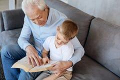 Homme impressionnant original enseignant sa lecture de petit-fils Photos libres de droits