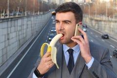 Homme inadéquat mordant une banane tout en appelant photos stock