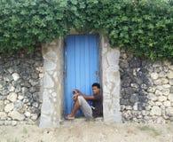 Homme inconnu s'asseyant à la porte Photographie stock libre de droits
